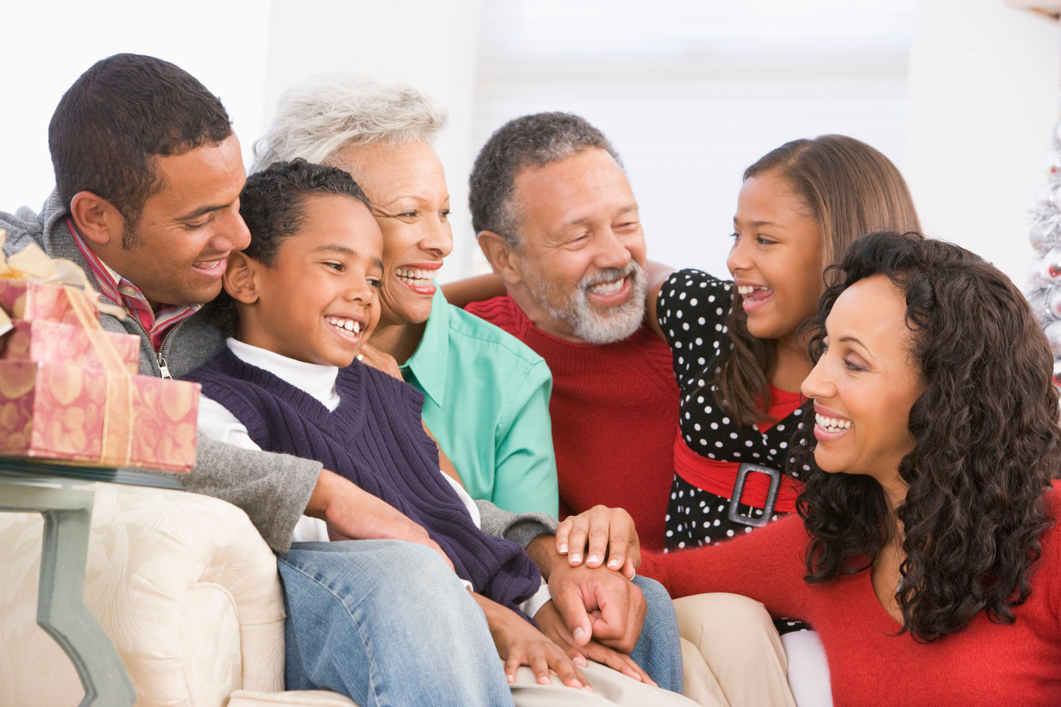 Three generations of a wealthy African-American family smiling together.